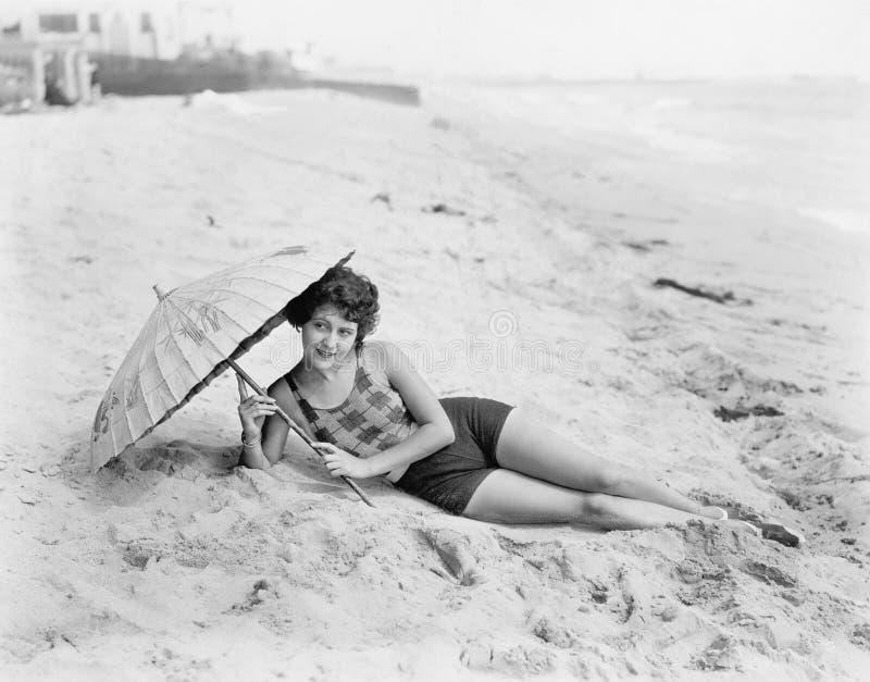 Kvinna som ligger på stranden med ett solparaply (alla visade personer inte är längre uppehälle, och inget gods finns Leverantörw fotografering för bildbyråer