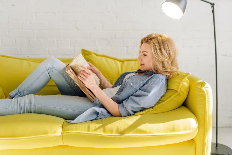 Kvinna som ligger p? den hemtrevliga gula soffan och l?seboken royaltyfri fotografi