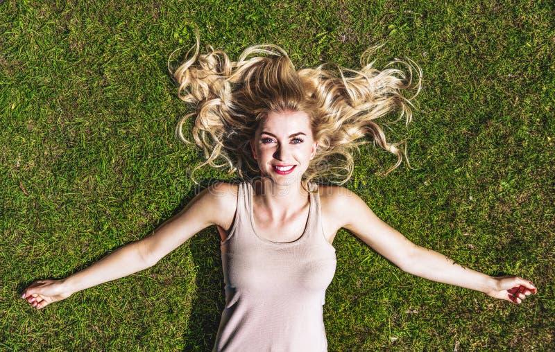 Kvinna som lugnar på gräs royaltyfri bild