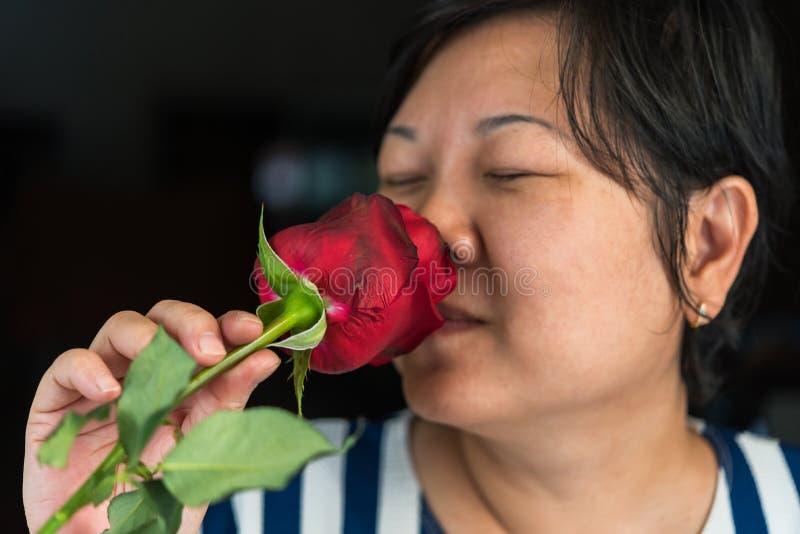Kvinna som luktar den röda rosblomman i dag för valentin` s arkivfoton