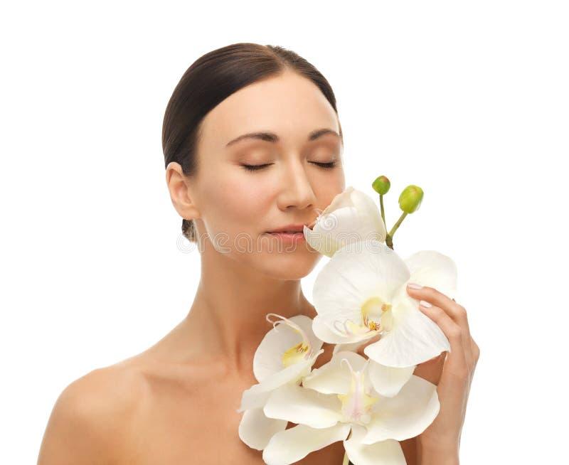 Kvinna som luktar den vita orkidéblomman royaltyfri bild