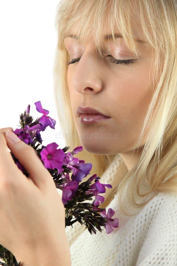 Kvinna som luktar gruppen av blommor royaltyfri bild