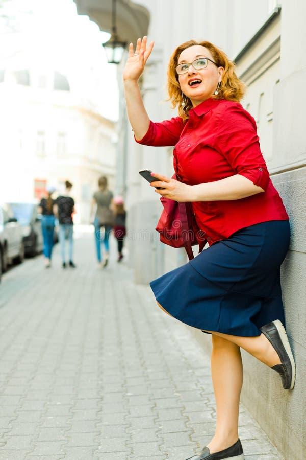 Kvinna som lutar mot v?ggen och anv?nder mobiltelefonen arkivfoton