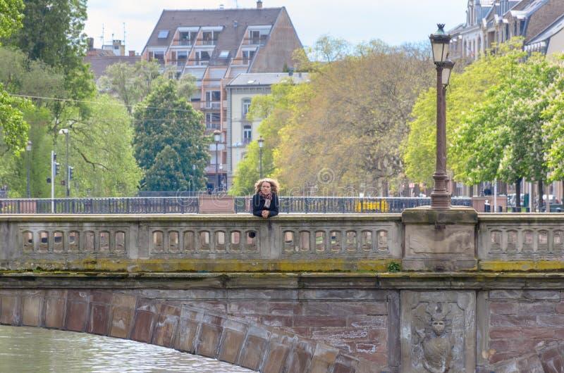 Kvinna som lutar på balustraden av en stenbro royaltyfria bilder