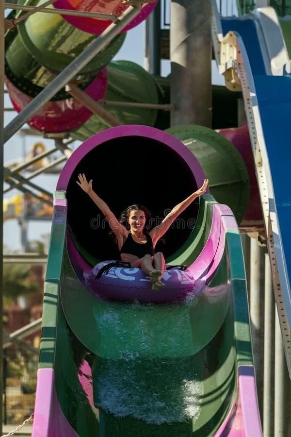 Kvinna som lyfter händer som har gyckel på rör vattenglidbanan royaltyfria foton