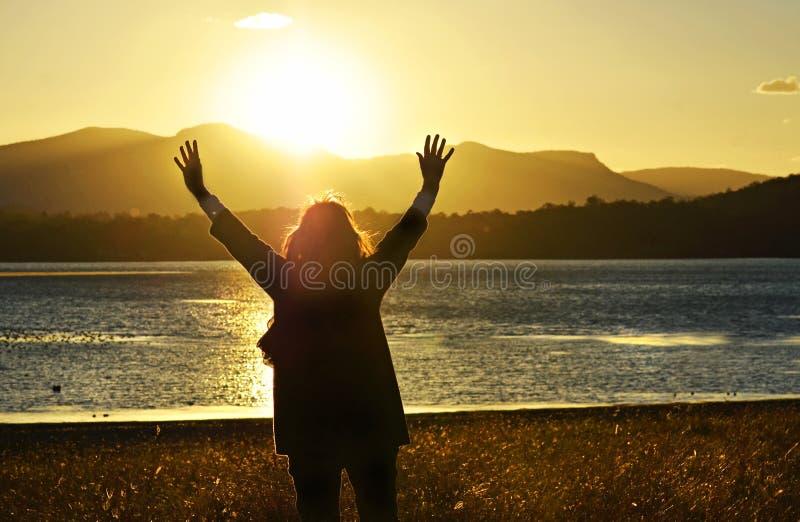 Kvinna som lyfter händer som tillber att lovorda be härlig solnedgång för gud arkivfoto