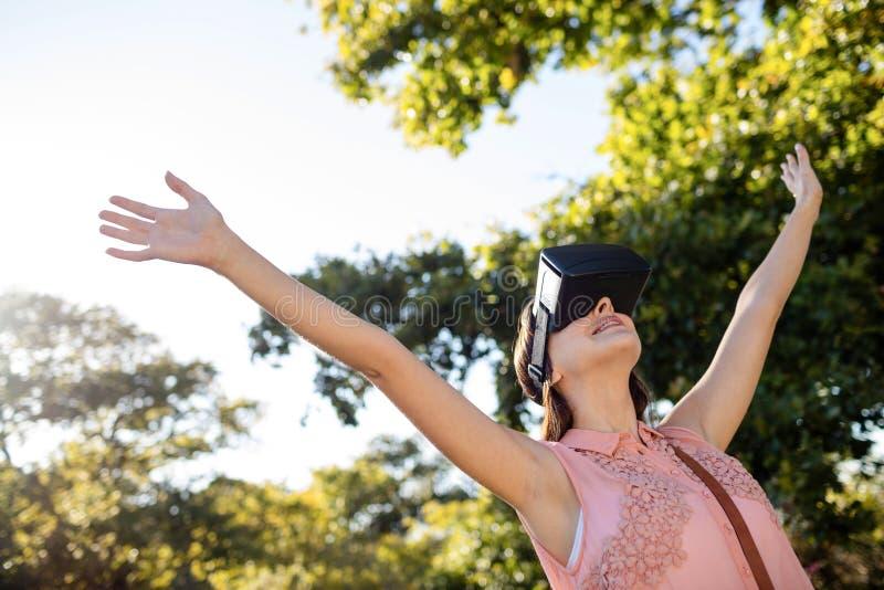 Kvinna som lyfter henne händer, medan genom att använda en VR-hörlurar med mikrofon i parkera arkivbilder