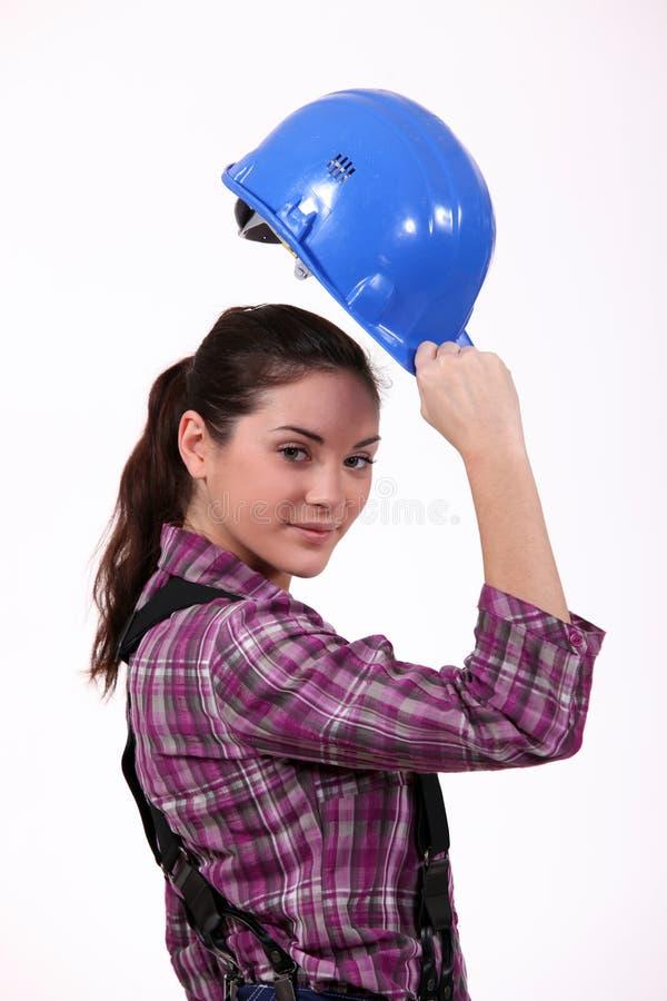 Kvinna som lyfter hennes hårda hatt royaltyfri foto