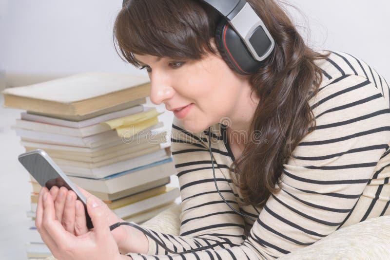 Kvinna som lyssnar en audiobook royaltyfri fotografi