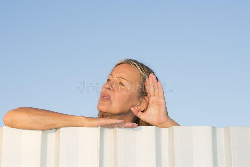 Kvinna som lyssnar för att låta utomhus- royaltyfri fotografi