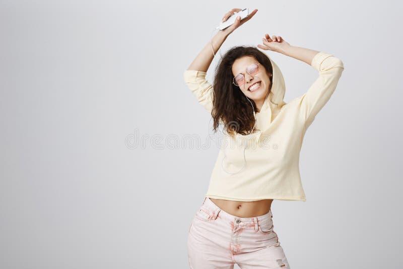 Kvinna som lyssnar hennes favorit- sång som ökar hennes lynne Studion sköt av positiv attraktiv europeisk lockig-haired flicka fotografering för bildbyråer