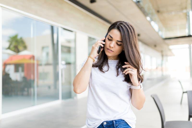 Kvinna som lyssnar till en appell på hennes mobiltelefon royaltyfria bilder