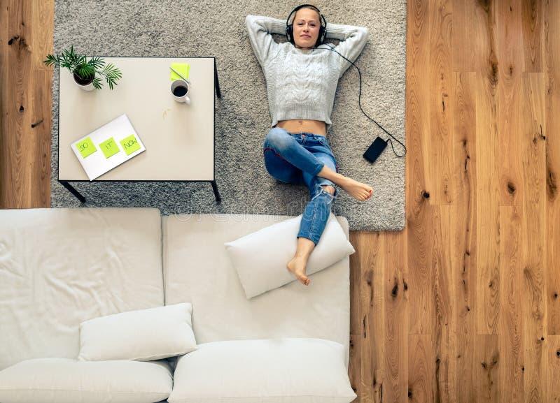 Kvinna som lyssnar till musik från den smarta telefonen genom att använda hörlurar arkivbilder