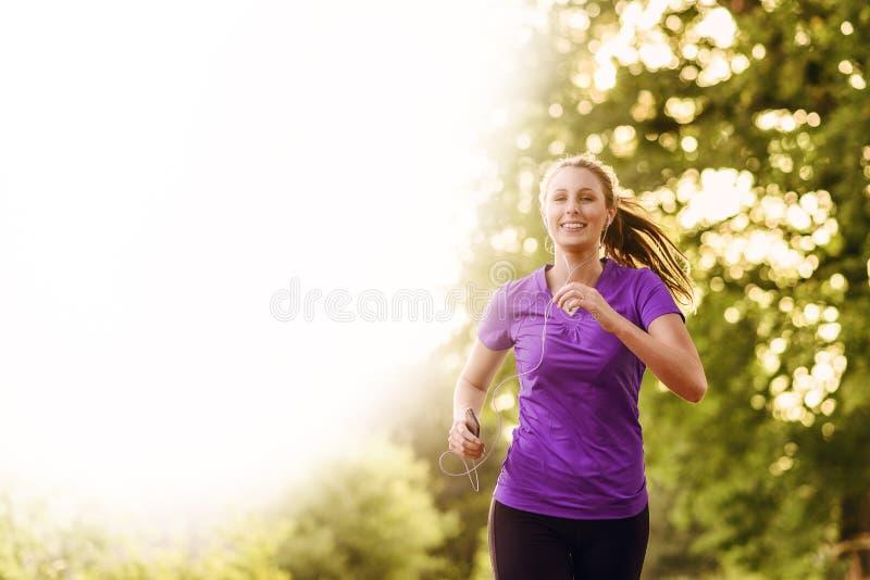 Kvinna som lyssnar till musik, medan jogga fotografering för bildbyråer