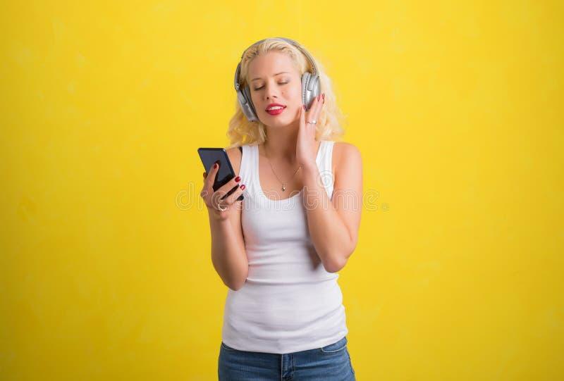 Kvinna som lyssnar till musik på trådlös hörlurar arkivfoto