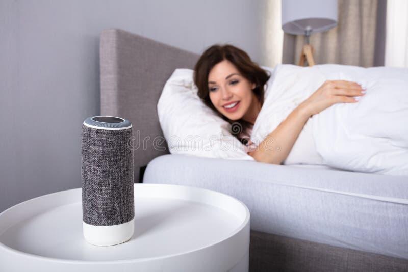 Kvinna som lyssnar till musik p? tr?dl?s h?gtalare royaltyfri fotografi