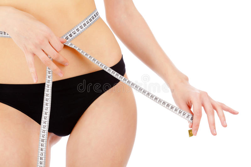 Kvinna som mäter henne waistline royaltyfria foton
