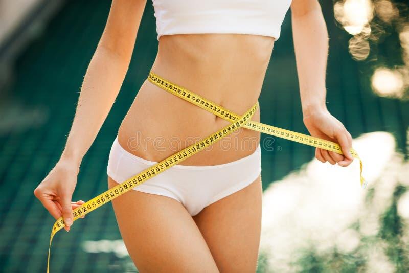 Kvinna som mäter henne waistline. Göra perfekt slankt förkroppsligar royaltyfria bilder