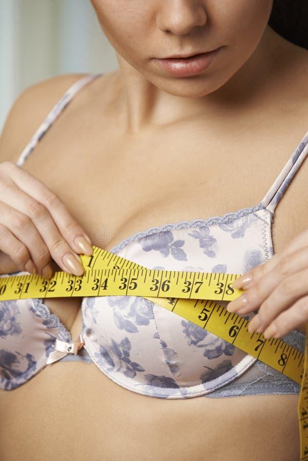 Kvinna som mäter hennes behåformat med måttband arkivfoton