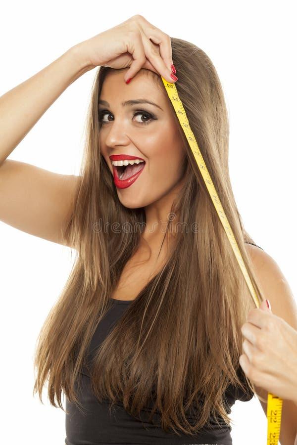 Kvinna som mäter hennes hår royaltyfria foton