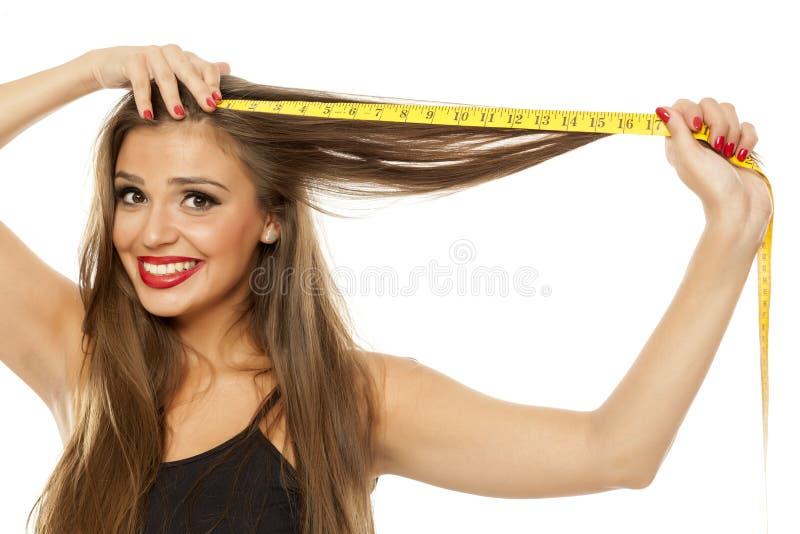Kvinna som mäter hennes hår fotografering för bildbyråer