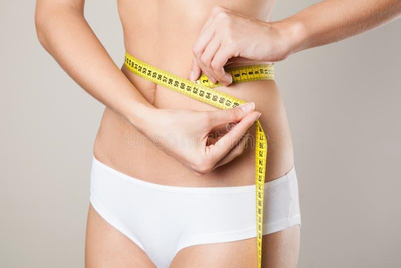 Kvinna som mäter hennes midja. Perfekt banta kroppen arkivfoto