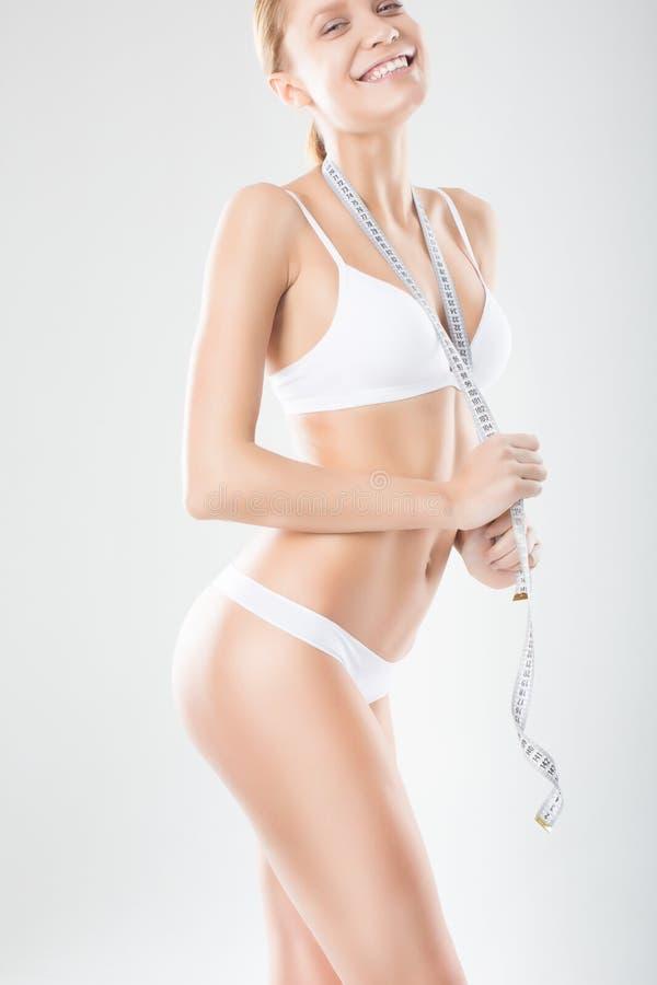 Kvinna som mäter hennes perfekta kropp på en vit bakgrund. Sunt arkivfoto