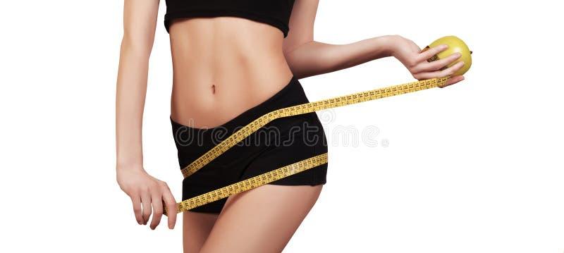 Kvinna som mäter hennes perfekta slanka kropp för midja banta Slank kropp som isoleras på vitt, kopieringsutrymme Färdig konditio royaltyfria foton