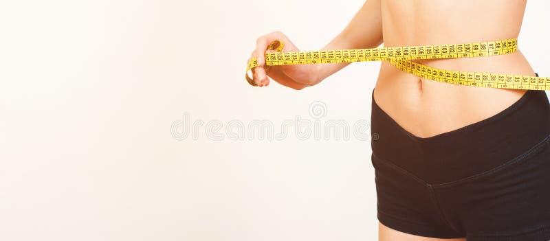 Kvinna som mäter hennes perfekta slanka kropp för midja banta Slank kropp som isoleras på vitt, kopieringsutrymme Färdig konditio fotografering för bildbyråer