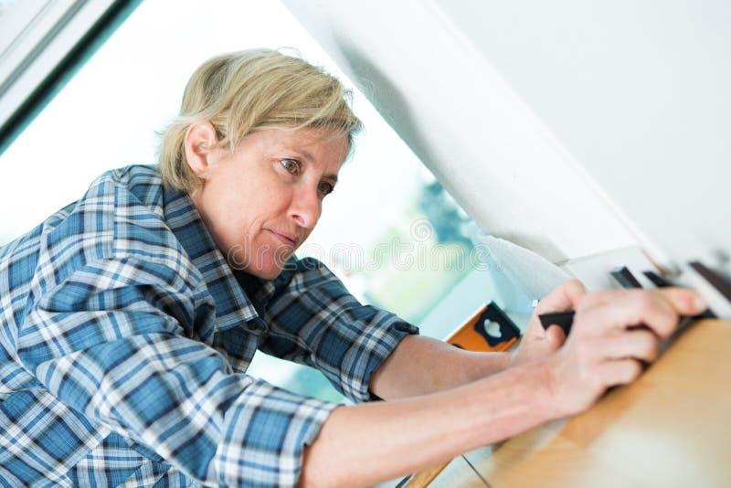 Kvinna som mäter träplankan med linjalen och blyertspennan arkivbilder