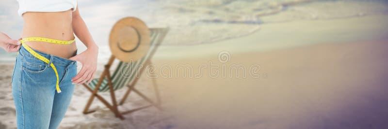 Kvinna som mäter vikt med att mäta bandet på midjan på sommarstranden med övergång arkivfoto