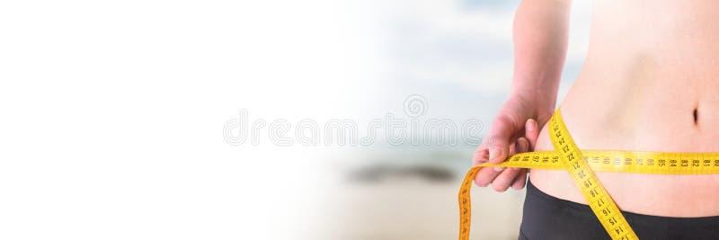 Kvinna som mäter vikt med att mäta bandet på midjan på sommarstranden med övergång fotografering för bildbyråer