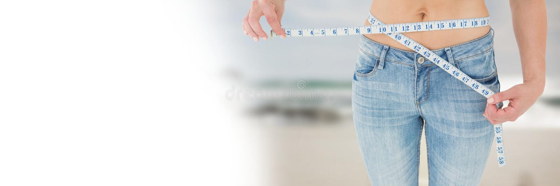 Kvinna som mäter vikt med att mäta bandet på midjan på sommarstranden med övergång royaltyfria bilder