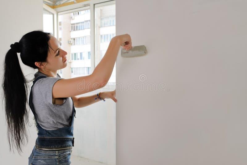 Kvinna som målar en lägenhet royaltyfria foton