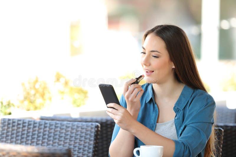 Kvinna som målar läppar med en telefon som spegel i en bar arkivfoto