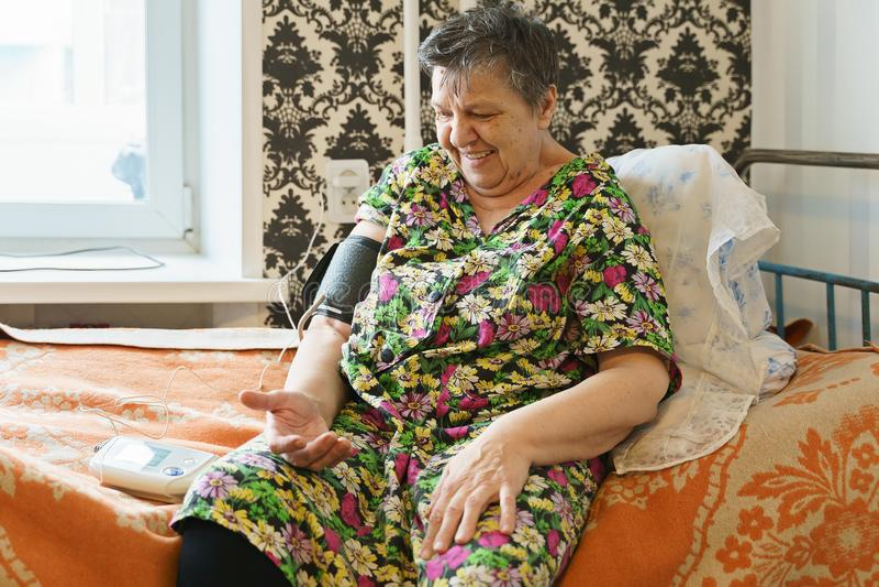 Kvinna som m?ter blodtryck med tonometer sj?lv royaltyfri fotografi