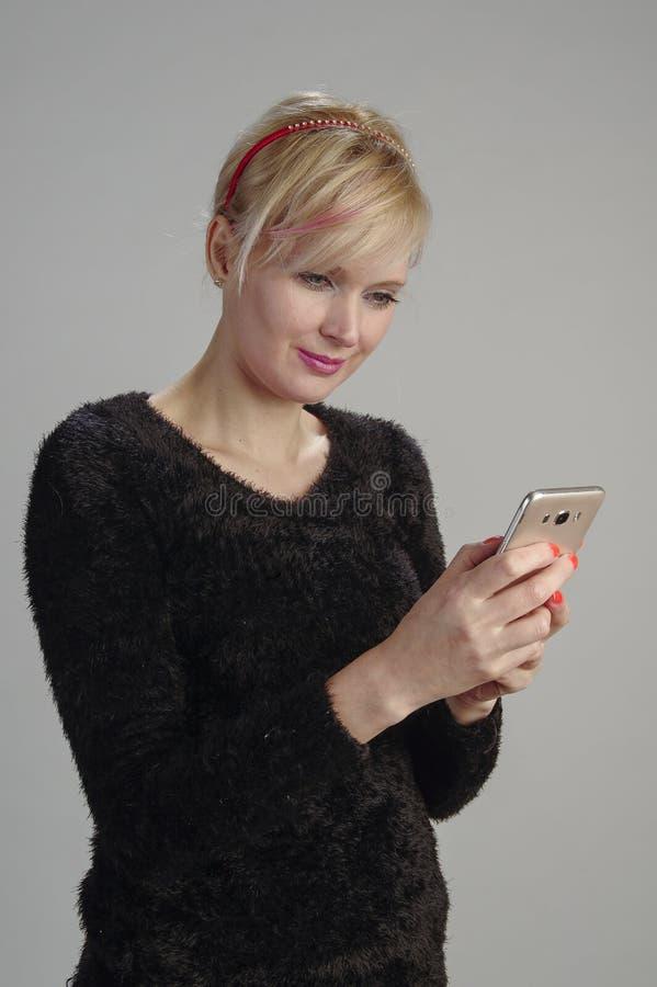 Kvinna som meddelar med mobilen arkivbild