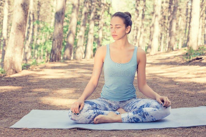 Kvinna som mediterar göra yoga arkivfoto