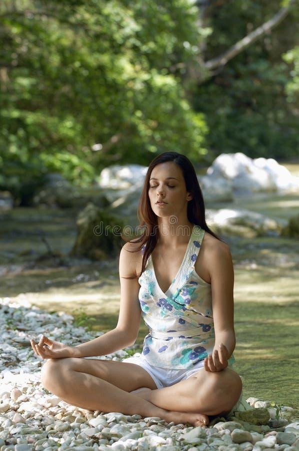 Kvinna som mediterar i Lotus Position By Forest River royaltyfri foto