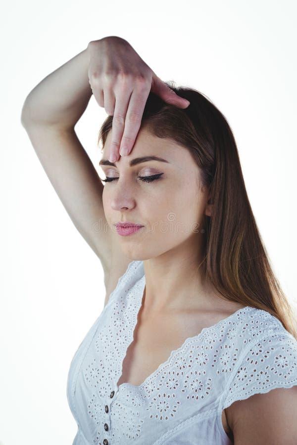 Kvinna som mediterar med handen på pannan royaltyfri bild