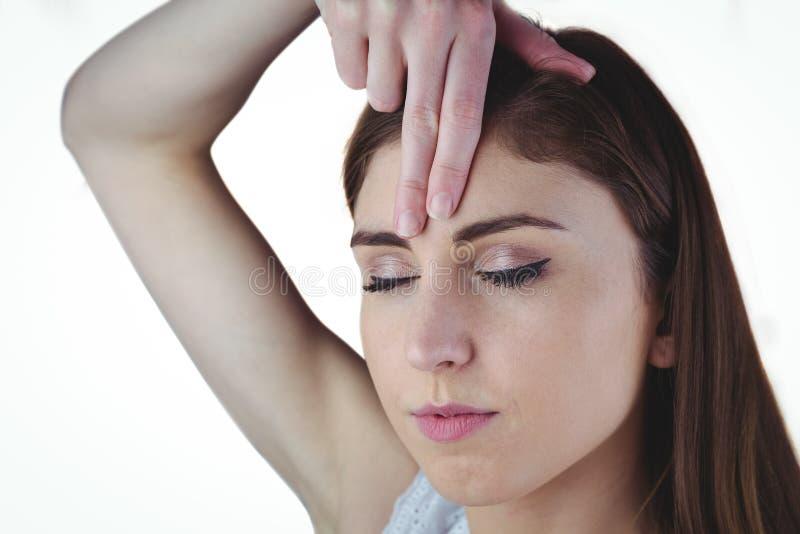 Kvinna som mediterar med handen på pannan arkivbilder
