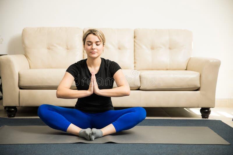 Kvinna som mediterar och gör någon yoga royaltyfri bild