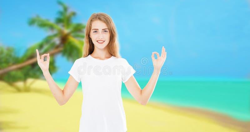 Kvinna som mediterar på tropiska Palm Beach händer upp Härlig kvinnlig modell som tycker om solen i dyrkan- och meditationzen öar royaltyfri foto