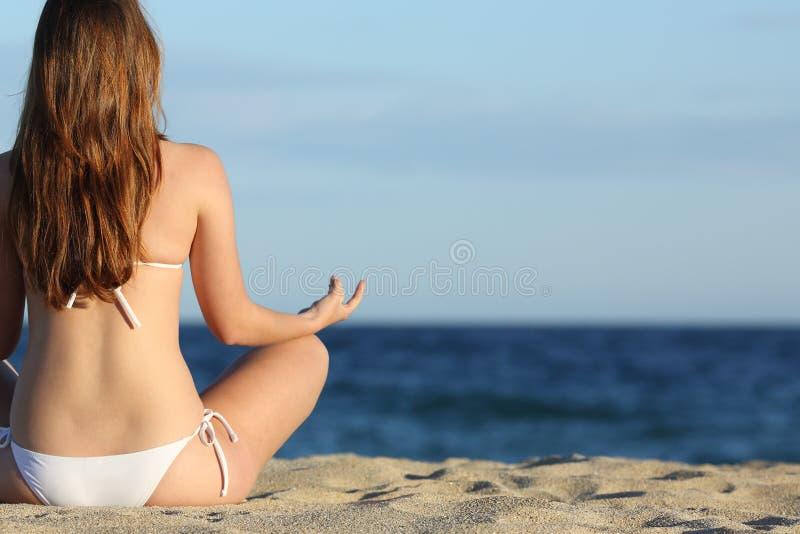 Kvinna som mediterar yoga på stranden i sommar arkivfoto