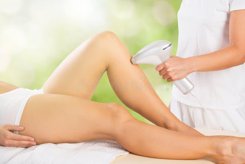 Kvinna som mottar behandling för laser Epilation på ben royaltyfria foton