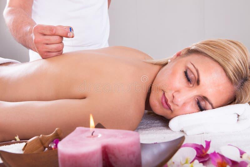 Kvinna som mottar en akupunkturterapi arkivbild