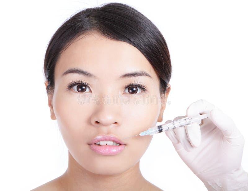 Kvinna som mottar en injektion i henne kant fotografering för bildbyråer