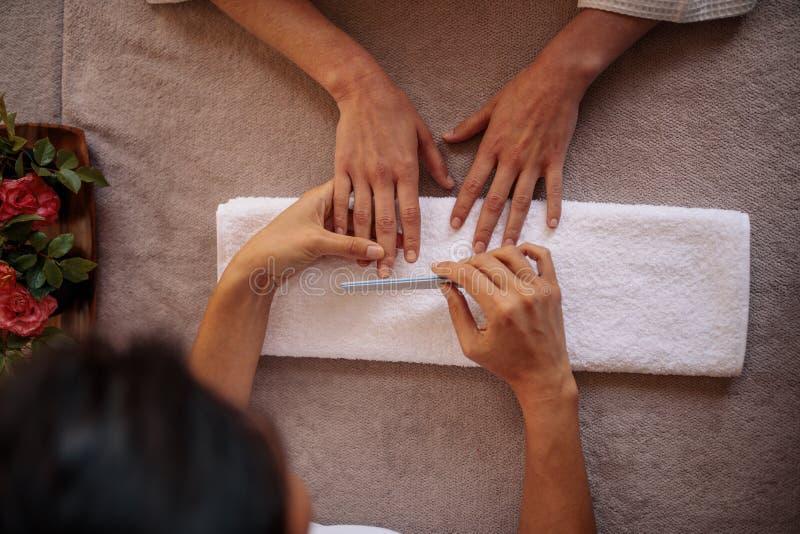 Kvinna som mottar en manikyr av kosmetologen i brunnsortsalong arkivbilder