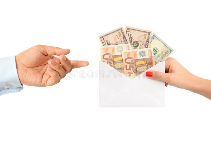 Kvinna som muter en man med ett kuvert som är fullt av pengar royaltyfri bild