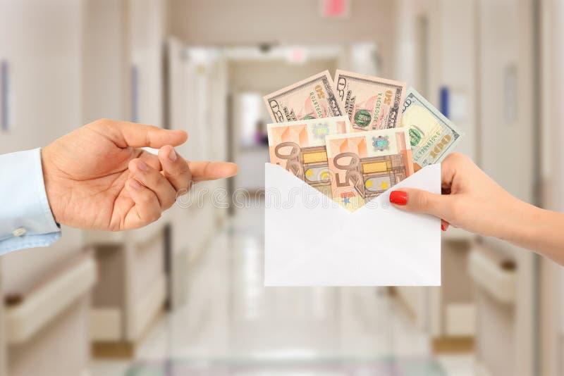 Kvinna som muter en man med ett kuvert som är fullt av pengar som föreslår en korrumperad vårdsystem arkivfoton
